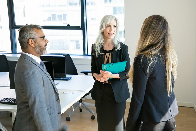 confident-partners-meeting-office-room-talking-smiling-bearded-boss-eyeglasses-discussing-project-with-beautiful-businesswomen-business-communication-top-management.jpg