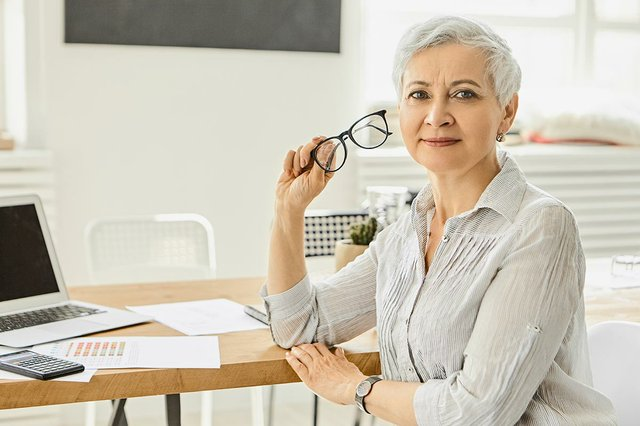 businesswoman-silky-gray-blouse-sitting-her-workplace-with-laptop-papers-calculator-desk-holding-glasses-having-break.jpg