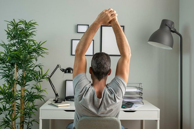 back-view-man-desk-stretching-working-from-home.jpg