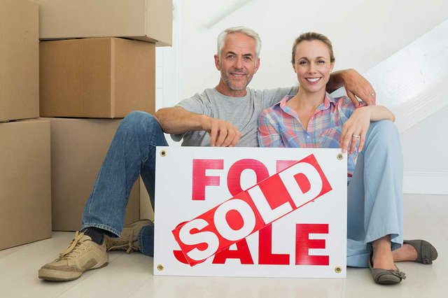 Happy-couple-sitting-on-floor-with-sold-sign.jpg
