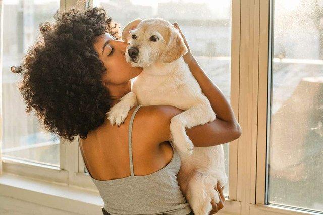woman-kissing-her-pet-dog-next-to-window.jpg