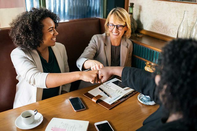 businesswomen-fist-bump-at-table.jpg