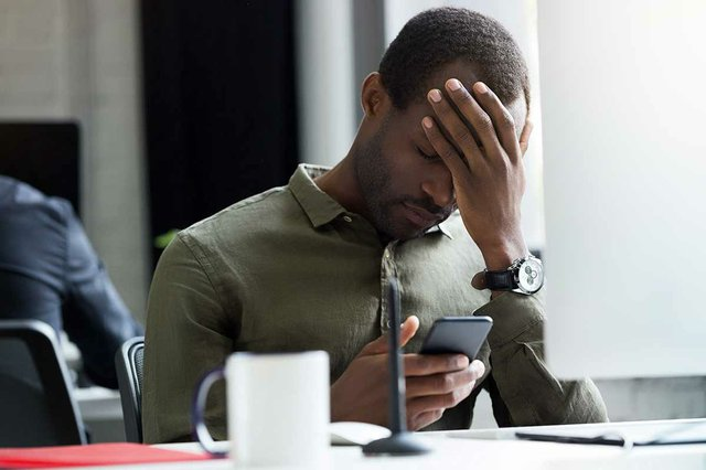 upset-young-man-reading-message-his-mobile-phone.jpg