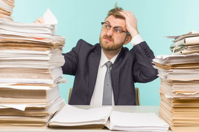 shocked-businessman-sitting-table-with-many-papers-office-is-overloaded-with-work-image.jpg