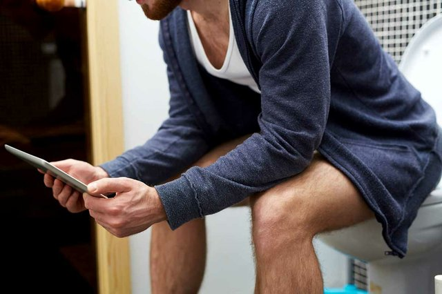 man-sitting-working-on-tablet-toilet.jpg