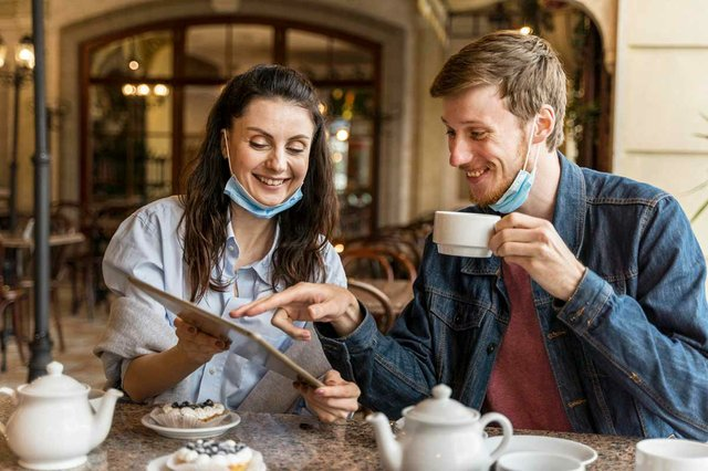 friends-chatting-restaurant-with-medical-masks-on-chin.jpg