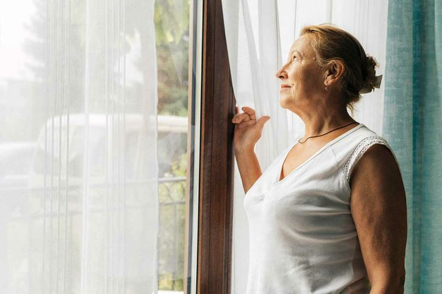 woman-home-during-pandemic-looking-through-window.jpg