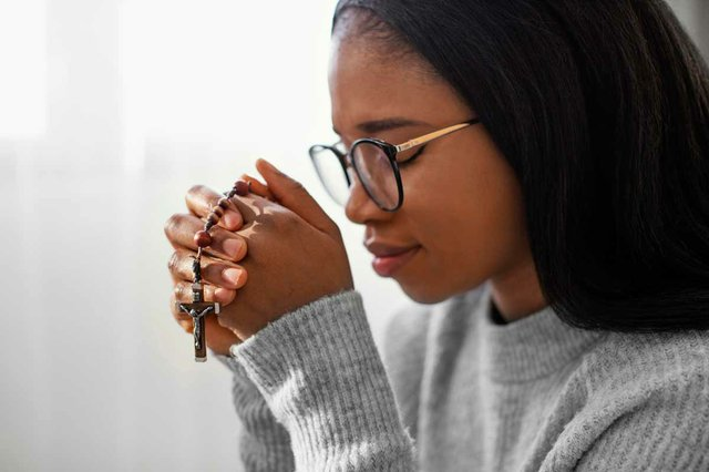 religious-woman-praying-holding-rosary-beads.jpg