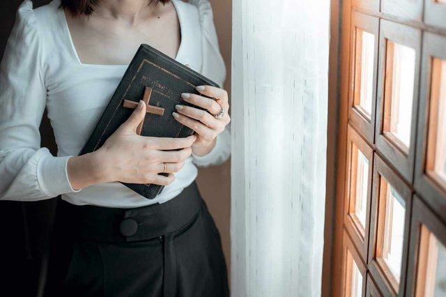 close-up-of-woman-hands-praying-with-bible-wooden-cross-church.jpg