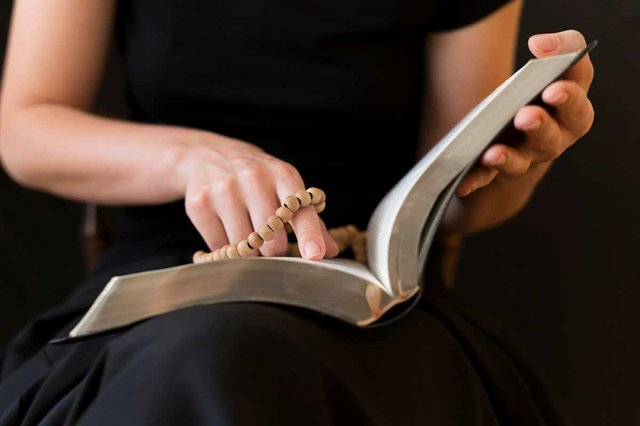 woman-reading-from-holy-book-while-holding-rosary.jpg
