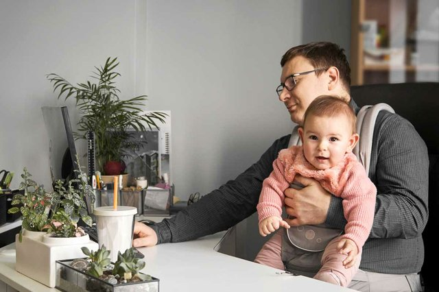 father-with-baby-carrier-working-office-home-with-computer-desk.jpg