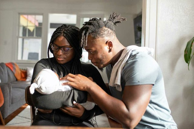 mother-holding-newborn-infant-as-smiling-father-looks-at-baby.jpg