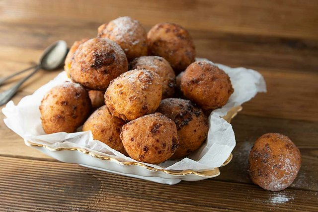 bunyols-de-vent-fried-doughnuts-on-white-decorative-plate-wood-table-background-and-two-spoons.jpg
