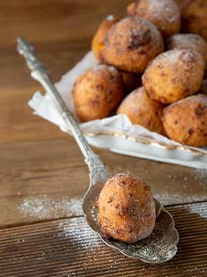bunyols-de-vent-fried-doughnuts-with-powdered-sugar-on-white-decorative-plate-wood-table-background-close-up.jpg