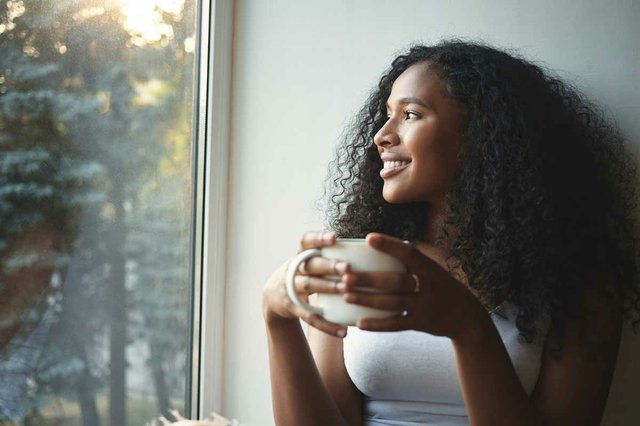 woman-sitting-windowsill-smiling-drinking-coffee.jpg