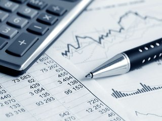 accounting concept close up of spreadsheet with calculator and pen.jpg