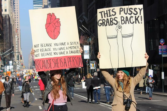 two-women-holding-cardboard-signs-in-support-of-womens-rights.jpg