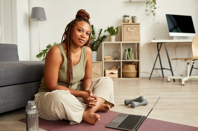 young-woman-sitting-exercise-mat-using-laptop-during-her-sport-training-home.jpg