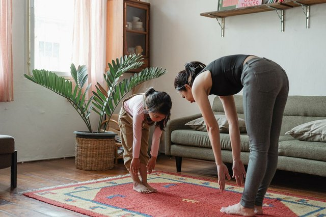 woman-at-home-with-daughter-exercising-in-livingroom.jpg