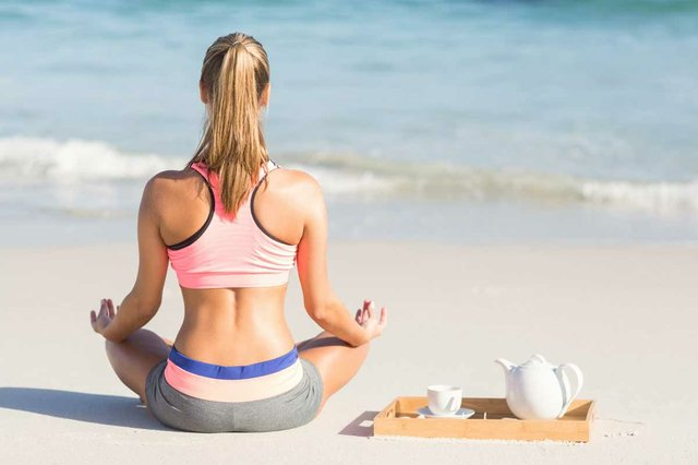 woman-doing-yoga-beside-sea-with-tray-and-tea-beside-her.jpg