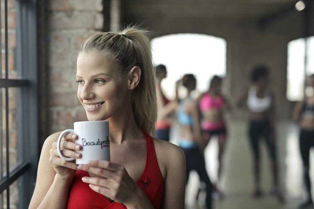 woman-at-gym-looking-out-windoe-drinking-coffee.jpg