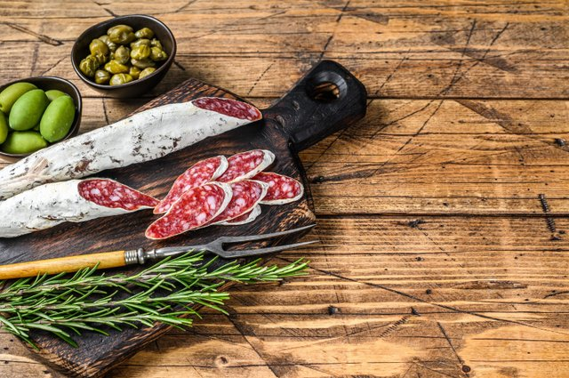 spanish-tapas-fuet-salami-sausage-slices-with-olives-rosemary-wooden-board-wooden-table-top-view.jpg