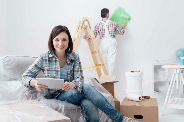 woman-on-sofa-looking-at-home-renovation-plan-mak-working-in-background.jpg