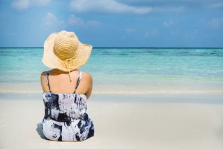 woman-in-hat-relaxes-on-the-beach.jpg