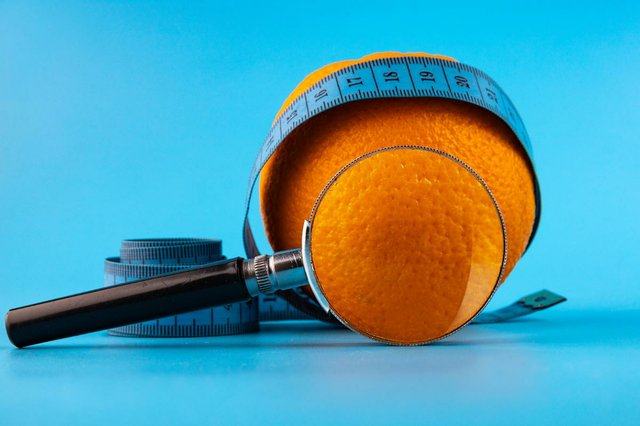 cellulite-concept-fresh-orange-with-magnifying-glass-blue-measuring-tape.jpg