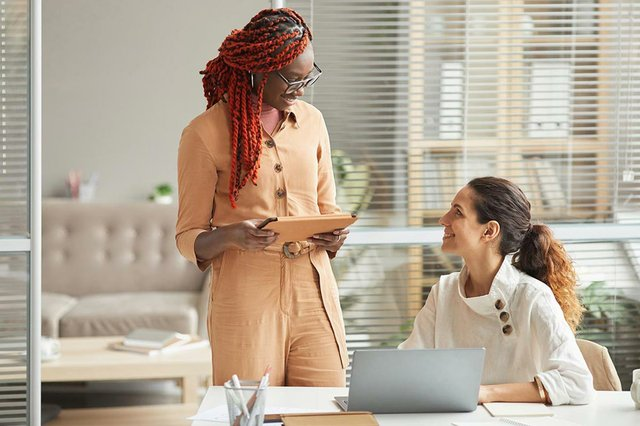 portrait-two-women-discussing-project-while-working-together-office.jpg