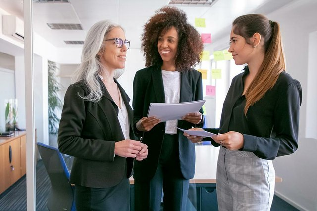 businesswomen-discussing-statistics-smiling-three-happy-attractive-female-colleagues-standing-with-papers-talking-conference-room-teamwork-business-management-concept.jpg