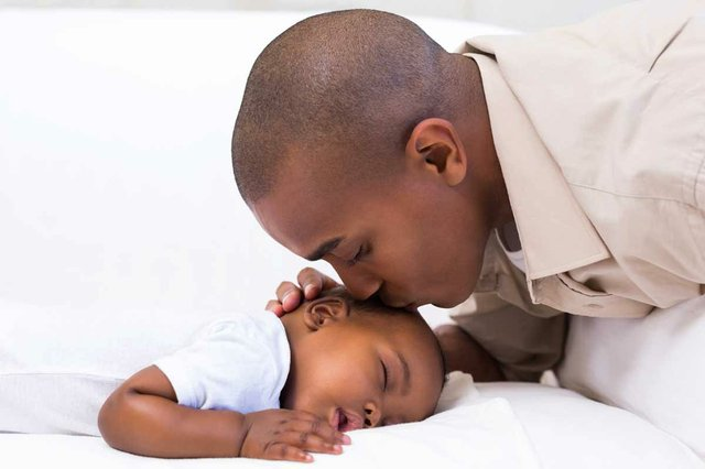 father-leaning-over-to-kiss-sleeping-baby-boy.jpg