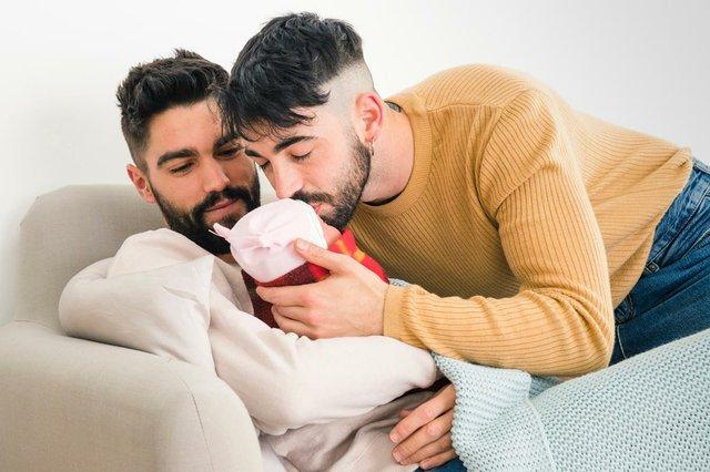 man-looking-at-his-boyfriend-kissing-their-sleeping-baby.jpg