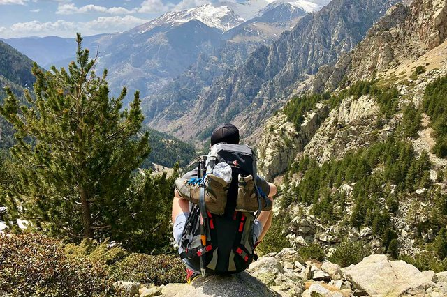 hiker-sitting-on-top-of-a-mountain-looking-down-at-valley-below.jpg
