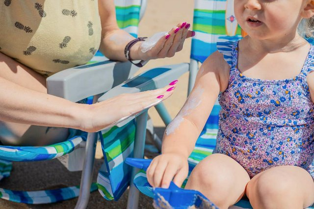 woman-applying-sunscreen-to-young-girl-playing-in-the-sand.jpg