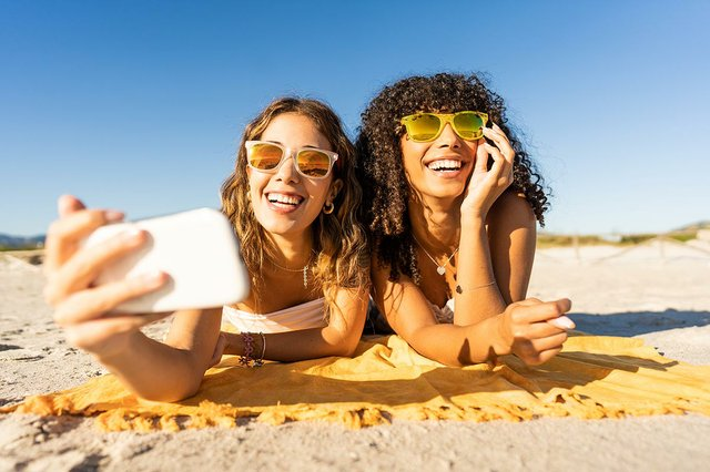 two-women-with-sunglasses-summer-vacation-using-smartphone-taking-selfie.jpg
