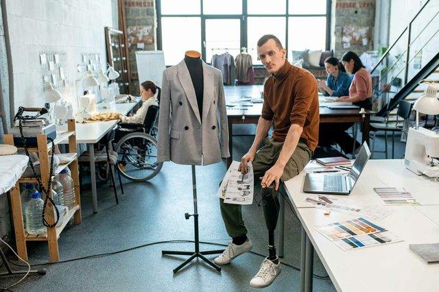 fashion-designer-tailor-with-prosthetic-leg-sitting-table-by-mannequin-inside-large-workshop.jpg