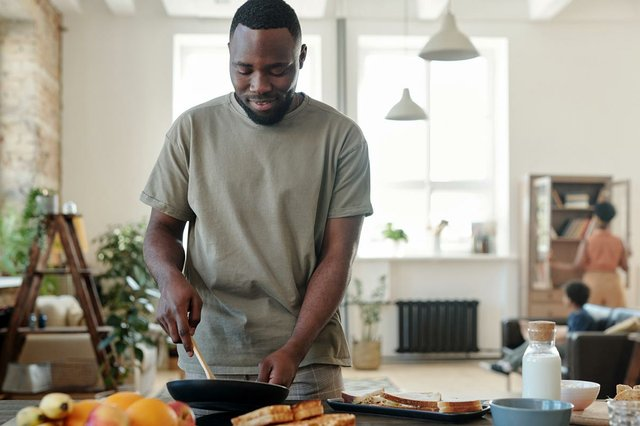man-cooking-at-electric-stove-kitchen-frying-something-himself-his-wife-their-little-son.jpg