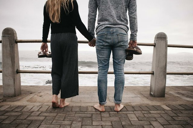 couples-holding-hands-on-a-boardwalk-along-the-seside-in-a-grey-day.jpg