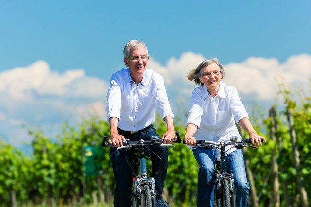 senior-couple-biking-summer-vineyard.jpg