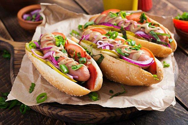 hot-dog-with-pickles-tomato-lettuce-wooden-background-hotdog.jpg