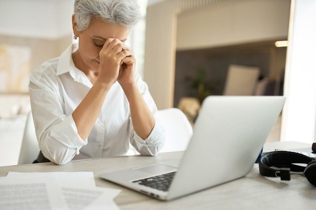 indoor-shot-frustrated-unhappy-middle-aged-businesswoman-managing-papers-while-sitting-office-desk-front-open-laptop-looking-down-with-hands-her-face.jpg