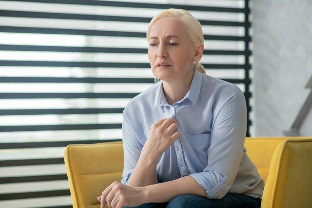 cadult-woman-with-blond-hair-sitting-chair-near-window.jpg