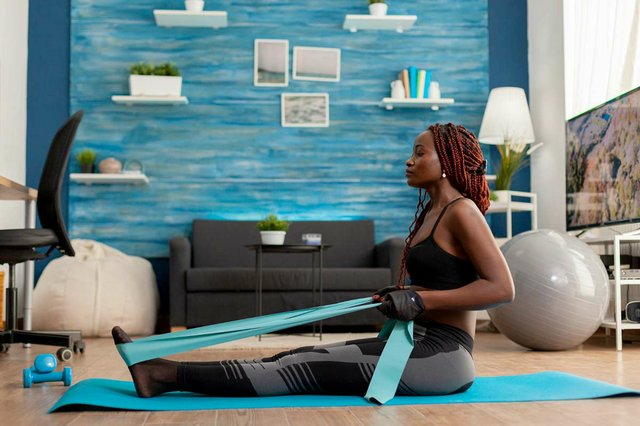 woman-training-home-living-room-using-resistance-band-sitting-fitness-mat-pulling-back-muscles.jpg