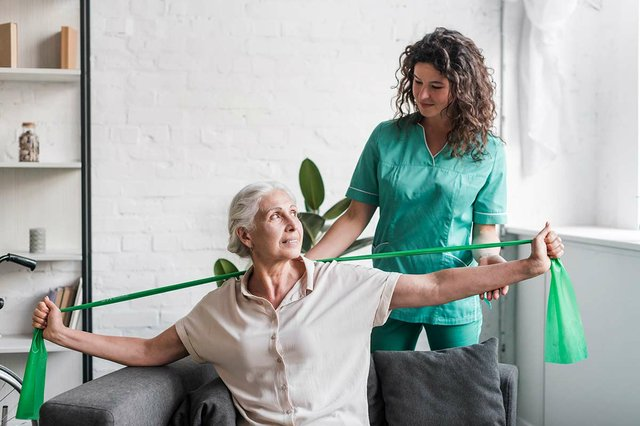 senior-woman-with-stretch-band-being-assist-by-female-physiotherapist.jpg