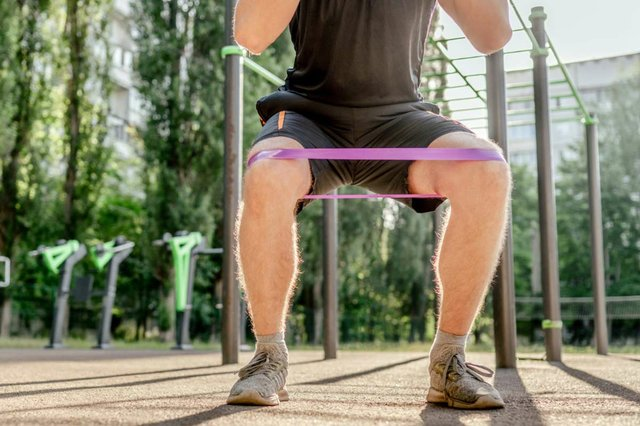 man-doing-squats-with-elastic-rubber-band-stadium-outdoors-adult-male-person-during-workout-legs-with-additional-sport-equipmant-exercising-outside.jpg