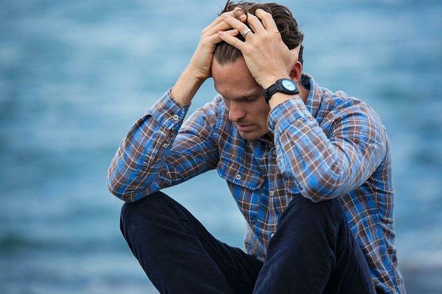 upset-man-in-blue-shirt-sitting-outside.jpg
